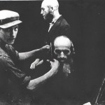 Chrzanower Shtibl, Auschwitz. Israel Lieb Bochner, son of Rabbi Aba Bochner of Sucha, having his peyos cut by a Jewish boy under the direction of the Nazi smoking a pipe at right.  Rabbi Jacob David Bornfriend stands at right with his beard already cut.  This photo was taken by someone in the Polish underground resistance and sent to Jacob after the war.