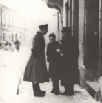 Jagielonska Street, Auschwitz, 1940.  An old Jewish man and a young Jewish girl are stopped by German policeman Schtreckenbach.  They are standing in front of Adam Kosyczark's house. In the left background, behind the sled, is Kluger's house, where Sternberg had a clothing store.  Further, is the entrance to Berka Joselewicza Street, and beyond that is Isaak Sadger's house and hardware store.