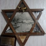 Star of David Frame, 1946. Wood.  Jacob designed the frame during his time at Kibbutz Nili just after the War.  He updated it with photos and keepsakes that were important to him after his journey to the US.  The center photo is Oswiecim town square on market day before the War.  In the points: American flag with Bald Eagle, and photos from their journey to America.