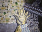 "NOW–THEN: NEVER AGAIN, 2014 Acrylic on canvas by Mollie Goldman   Grade 9, Fuchs Mizrachi School  The artist writes, ""This painting describes the perspective of a young boy who survived the Holocaust. The smaller hand is his younger self, overlaid on top of the hand of his older self. The background also symbolizes the present and the past.  The bright stones of the Wall are meant to specifically contrast the Jewish gravestones that were desecrated and used to pave roads during the Holocaust. Hope vs. Horror. The tattoo is actually a real number. When I was about to paint the number, I read an article by Regina Brett published in the Cleveland Jewish News that highlighted one man's story.  Brett wrote: 'Holocaust survivor Jacob Hennenberg … found hope in the camps in the tattoo the Nazis engraved on his arm. The numbers 64242 added up to 18, which in Hebrew stands for ""life."" Jacob decided that meant he would live.'  In honor of Mr. Hennenberg, I chose to use his number."